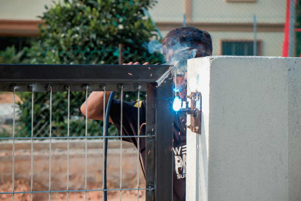 Privacy fences: A construction worker uses arc welding to build a metal gate for a new home